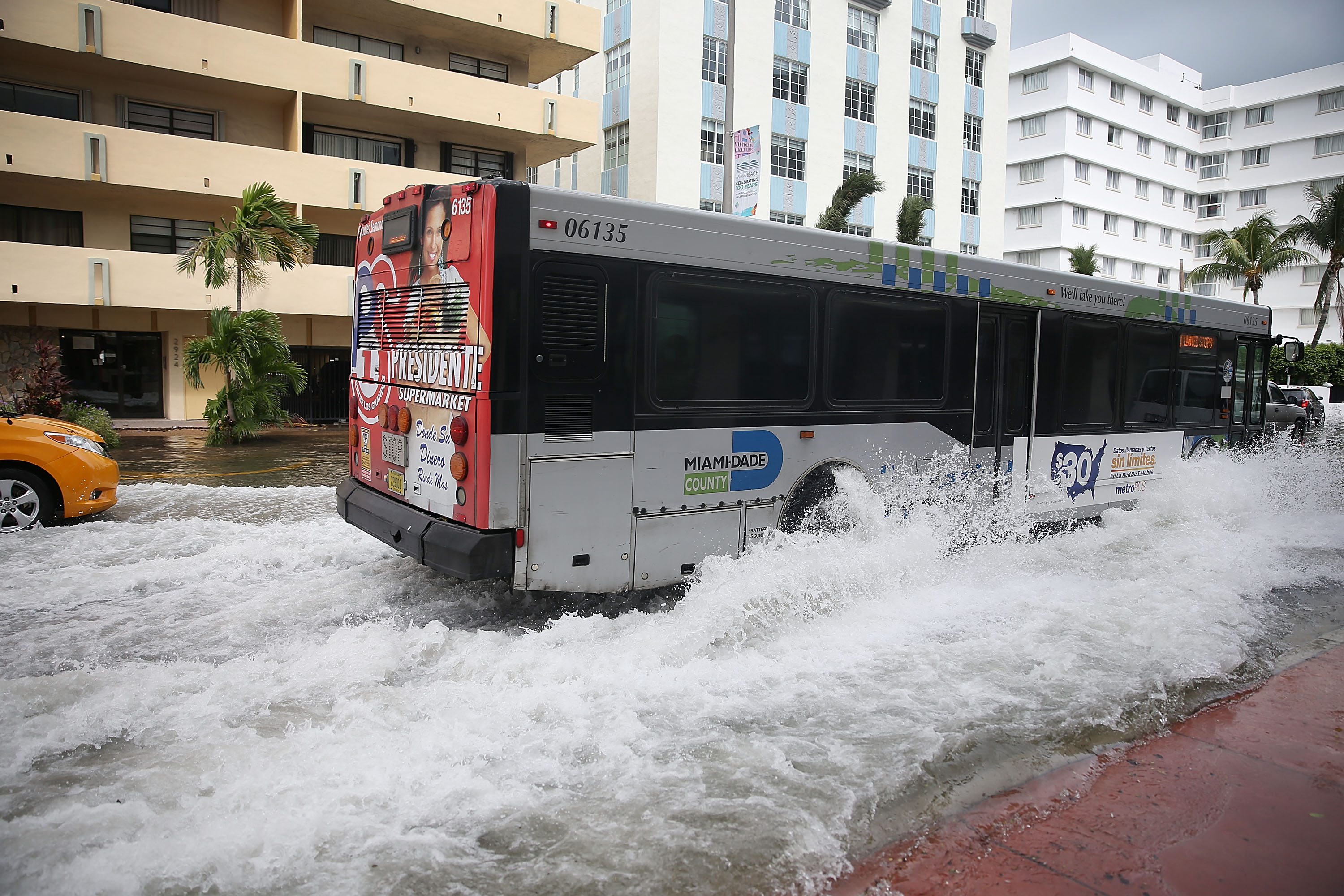 MIAMI BEACH, FL - SEPTEMBER 29: A bus plows through a flooded street that was caused by the combination of the lunar orbit which caused seasonal high tides and what many believe is the rising sea levels due to climate change on September 29, 2015 in Miami Beach, Florida. The City of Miami Beach is in the middle of a five-year, $400 million storm water pump program and other projects that city officials hope will keep the ocean waters from inundating the city as the oceans rise even more in the future. (Photo by Joe Raedle/Getty Images)
