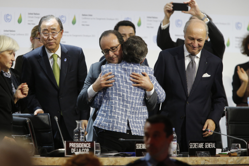 Executive Secretary of the United Nations Framework Convention on Climate Change (UNFCCC) Christiana Figueres (C-R) and France's President Francois Hollande (C-L) hug after the adoption of a historic global warming pact at the COP21 Climate Conference in Le Bourget, north of Paris, on December 12, 2015. Envoys from 195 nations on December 12 adopted to cheers and tears a historic accord to stop global warming, which threatens humanity with rising seas and worsening droughts, floods and storms. AFP PHOTO / FRANCOIS GUILLOT / AFP / FRANCOIS GUILLOT (Photo credit should read FRANCOIS GUILLOT/AFP/Getty Images)