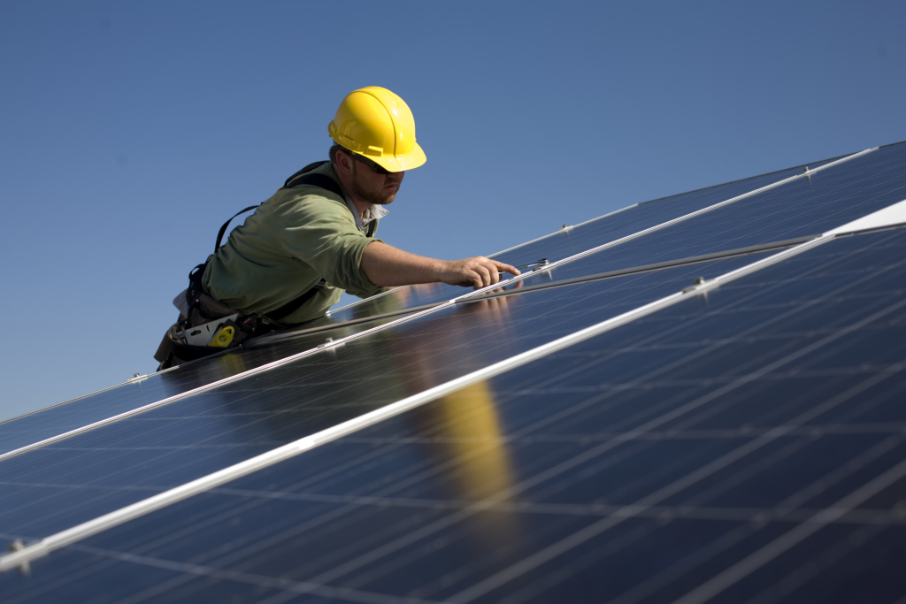 A worker installing solar panels on a rooftop in Pleasanton, California. (Robert Nickelsberg/Getty Images)